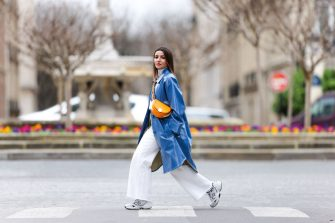 PARIS, FRANCE - MARCH 05: Alexandra Pereira wears a white turtleneck pullover / sweater from Zara, a blue long trench coat from Stand Studio, white flare denim jeans from Zara, an orange half-moon semi-circular bag from Fendi, white sneakers shoes from New Balance, on March 05, 2021 in Paris, France. (Photo by Edward Berthelot/Getty Images)