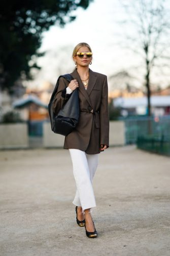 PARIS, FRANCE - JANUARY 21: Caroline Daur wears earrings, mirrored sunglasses, necklaces, a brown jacket, white crop ripped hem pants, black quilted shoes with gold-tone tips, a black bag, outside Alexandre Vauthier, during Paris Fashion Week - Haute Couture Spring/Summer 2020, on January 21, 2020 in Paris, France. (Photo by Edward Berthelot/Getty Images )