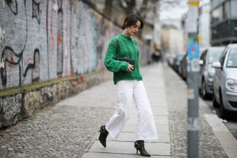 BERLIN, GERMANY - MARCH 19: Frankie Miles wearing sunglasses Celine, green knit ba&sh, white jeans culotte H&M, statement earrings topshop, clutch solitaire miu miu, Cowboy Boots gestuz on March 19, 2019 in Berlin, Germany. (Photo by Jeremy Moeller/Getty Images)