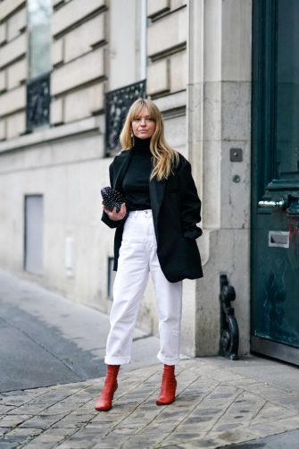 PARIS, FRANCE - FEBRUARY 28: Jeanette Madsen wears earrings, a black turtleneck pullover, a black oversized blazer jacket, white pants, red leather boots, a black bag with polka dots, outside Alessandra Rich, during Paris Fashion Week - Womenswear Fall/Winter 2020/2021, on February 28, 2020 in Paris, France. (Photo by Edward Berthelot/Getty Images)