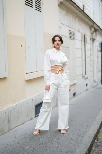 PARIS, FRANCE - APRIL 28: Ketevan Giorgadze @katie.one wears a cropped tie waist shirt from Le Ger, mid rise wide leg ripped denim jeans in white from Le Ger, a Le chiquito white mini leather bag from Jacquemus, strappy low heeled sandals in white from Raye, on April 28, 2021 in Paris, France. (Photo by Edward Berthelot/Getty Images)