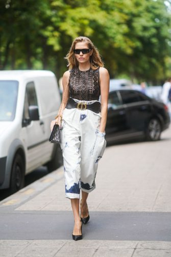 PARIS, FRANCE - JULY 01: Lena Perminova wears black sunglasses, a golden bracelet, a black lace top, a large DIor belt, tie-and-dye white crop pants, a Dior monogram bag, black pointy heeled pumps, outside Dior, during Paris Fashion Week -Haute Couture Fall/Winter 2019/2020, on July 01, 2019 in Paris, France. (Photo by Edward Berthelot/Getty Images)