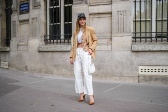 PARIS, FRANCE - MAY 16: Natalia Verza @mascarada.paris wears, a black leather cap, a beige linen oversized blazer jacket from Aeron, a white cropped t-shirt, white ripped denim jeans pants, a white Prada Cleo bag, high heels pointed pumps shoes from Louboutin, on May 16, 2021 in Paris, France. (Photo by Edward Berthelot/Getty Images)