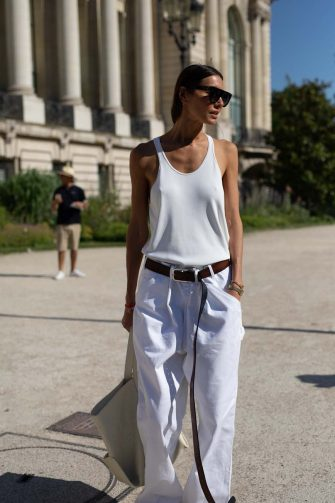PARIS, FRANCE - JULY 02: A guest is seen on the street during Paris Fashion Week Haute Couture wearing white tank top, white pants, oversize brown belt, cream tote bag and sandals on July 02, 2019 in Paris, France. (Photo by Matthew Sperzel/Getty Images)