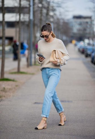 DUSSELDORF, GERMANY - FEBRUARY 06: Ann-Kathrin Götze is seen looking on her Apple Iphone 12 wearing beige Ferragamo jumper, denim jeans Saint Laurent, Chanel bag and shoes in beige, sunglasses Dior on February 06, 2021 in Dusseldorf, Germany. (Photo by Christian Vierig/Getty Images)