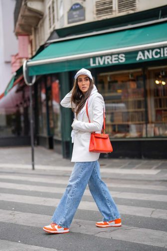 PARIS, FRANCE - APRIL 30: Tamara Kalinic wears a white Celine cap, a white latte ribs tank top, a white long Saint Laurent YSL blazer jacket, a white embroidered Chanel sweater, a red shiny leather Kelly Hermes handbag, blue faded denim boyfriend jeans Margiela pants, red and white shiny leather Nike Air Force 1 sneakers, on April 30, 2021 in Paris, France. (Photo by Edward Berthelot/Getty Images)