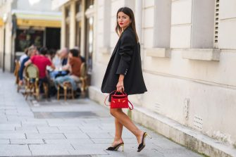 PARIS, FRANCE - JUNE 21: Alexandra Pereira wears gold earrings, an oversized long black blazer jacket from The Frankie Shop, a gold chain belt from Chanel, black ripped denim jeans shorts from Zara, silver and diamonds rings, a red shiny leather small Kelly handbag from Hermes, black suede open toe-cap pumps gold heels shoes / sandals from Bettina Vermillon, on June 21, 2021 in Paris, France. (Photo by Edward Berthelot/Getty Images)