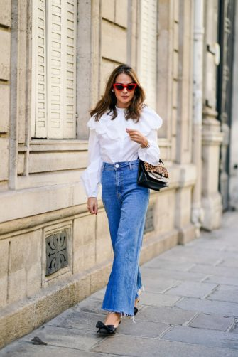 PARIS, FRANCE - SEPTEMBER 15: Therese Hellström wears red Celine sunglasses, a white shirt / blouse from H&M with large ruffled collar, a black leather Karl Lagerfeld bag with a chain and brown leopard print, blue denim flared jeans from Zara, pointy shoes with bow tie from Custommade, on September 15, 2020 in Paris, France. (Photo by Edward Berthelot/Getty Images)