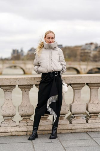 PARIS, FRANCE - FEBRUARY 27: Thora Valdimars wears a white winter puffer coat, a black skirt with fringes, black leather boots, a Maison Margiela white bag, outside Paco Rabanne, during Paris Fashion Week - Womenswear Fall/Winter 2020/2021, on February 27, 2020 in Paris, France. (Photo by Edward Berthelot/Getty Images)