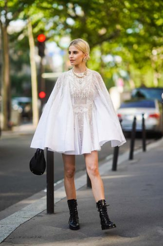 PARIS, FRANCE - JULY 01: Caroline Daur wears earrings, a necklace, a white ruffled lace mesh dress, black boots, a black bag, outside Giambattista Valli, during Paris Fashion Week -Haute Couture Fall/Winter 2019/2020, on July 01, 2019 in Paris, France. (Photo by Edward Berthelot/Getty Images)