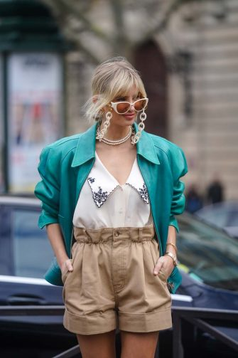 PARIS, FRANCE - MARCH 03: Xenia Adonts wears a green leather jacket with shoulder pads, a low neck shirt with printed flowers on the collar, pale brown shorts, a pearl necklace, sunglasses with chains, outside Miu Miu, during Paris Fashion Week - Womenswear Fall/Winter 2020/2021 on March 03, 2020 in Paris, France. (Photo by Edward Berthelot/Getty Images)