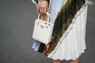 PARIS, FRANCE - AUGUST 02: Gabriella Berdugo wears a pleated midi skirt with printed landscape details from Icicle, a white Prada bag, on August 02, 2021 in Paris, France. (Photo by Edward Berthelot/Getty Images)