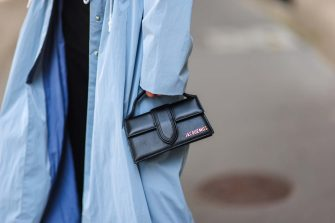 PARIS, FRANCE - AUGUST 15: Julia Comil wears a Long baby blue rain coat with drawstrings by Remain Birger Christensen, a Bambino black handbag by Jacquemus, on August 15, 2021 in Paris, France. (Photo by Edward Berthelot/Getty Images)