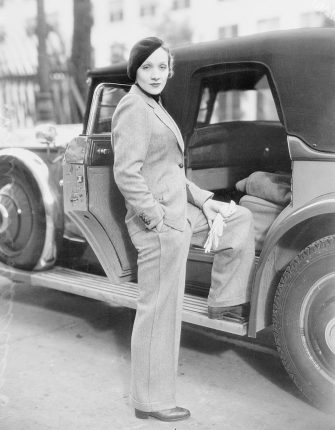 Wearing a beret and carrying gloves, Marlene Dietrich, prominent Paramount screen star, jauntily strolls along Hollywood Street attired in a grey man's suit, with turtle-neck sweater. Stylists declare this mode set by Marlene will sweep the country--which probably means that men will have to find themselves some cute tailored skirts.