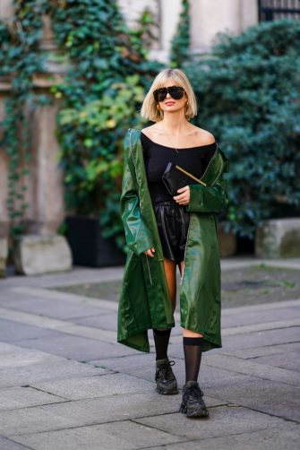 MILAN, ITALY - FEBRUARY 20: Xenia Adonts wears aviator sunglasses, a black off shoulder top, a green trench coat, a black leather mini skirt, outside Koche x Pucci, during Milan Fashion Week Fall/Winter 2020-2021 on February 20, 2020 in Milan, Italy. (Photo by Edward Berthelot/Getty Images)