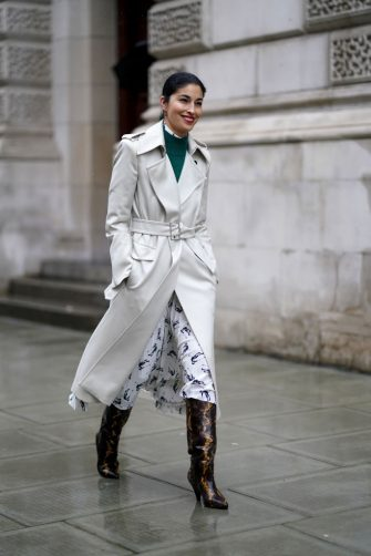 LONDON, ENGLAND - FEBRUARY 16: Caroline Issa wears a green pullover, a white long trench coat, a dress, black and brown pointy snake pattern printed boots, during London Fashion Week Fall Winter 2020 on February 16, 2020 in London, England. (Photo by Edward Berthelot/Getty Images)