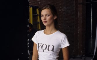 """NEW YORK - 1995:  British Supermodel Kate Moss, wearing a t-shirt printed with the word """"You"""" enjoys a quiet moment during a fashion shoot at a photo studio in 1995 in New York City, New York. (Photo by Catherine McGann/Getty Images)"""