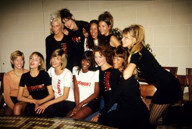 """PARIS, FRANCE - JANUARY 01: Nadja Auermann, Carla Bruni,  Amber Valletta  ( 2nd on Below rank  ), Linda Evangelista, Naomi Campbell, Shalom Harlow, Claudia Schiffer  and Top Models """" Fashion Aid Clothing """" Tee Shirts Pose at the Versace High Fashion Show at the Ritz Hotel on January 1,1994 in Paris, France. ( Photo by Foc Kan/Wireimage )"""