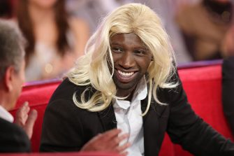 """French actor Omar Sy wears a wig as he takes part in the TV show """"Vivement Dimanche"""" on December 5, 2012 on a set of French TV France 2 in Paris. AFP PHOTO THOMAS SAMSON        (Photo credit should read THOMAS SAMSON/AFP via Getty Images)"""