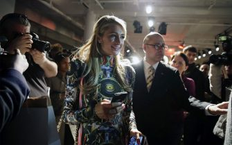epa04073205 US socialite Paris Hilton (C) is escorted by security while being trailed by a photographer at the conclusion of the Fall/Winter 2014 collection by The Blonds during Mercedes-Benz Fashion Week in New York, New York, USA, 12 February 2014. The Fall Winter 2014 collections are presented from 06 to 13 February.  EPA/JASON SZENES