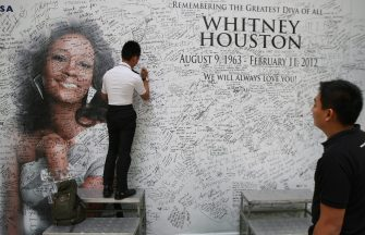 epa03108177 A Filipino fan signs a message wall with the image of late US singer Whitney Houston at a shopping mall in Quezon City, east of Manila, Philippines 16 February 2012. Houston, a Grammy Award winning singer, was found dead in her hotel room in Beverly Hills, California, USA on 11 February. She died at the age of 48.  EPA/ROLEX DELA PENA