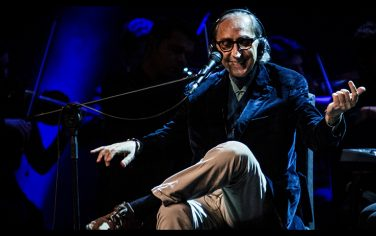 Italian singer-songwriter Franco Battiato on the stage in Milan with Italian singer Alice (Carla Bissi), in concert for a date of the national tour. The event celebrates their artistic partnership that began in the 1980s. They are singing together the hits born from a long-lasting artistic history. From the left: Battiato sitting at the microphone with crossed legs and open arms while performing. Arcimboldi Theatre, Milan, Italy, 8th March 2016. (Photo by  Francesco Castaldo\Archivio Francesco Castaldo\Mondadori via Getty Images)