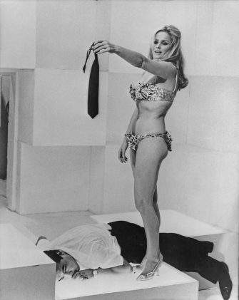 Actress Ursula Andress wearing a bikini and high heels while her outstretched hand holds a tie, a man lies beneath her, circa 1965. (Photo by American Stock Archive/Archive Photos/Getty Images)