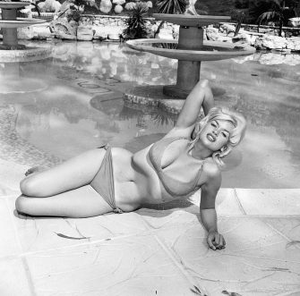 American film actor and sex symbol Jayne Mansfield (1933 - 1967) lounges provocatively in a bikini near a pool, mid 1950's. (Photo by Hulton Archive/Getty Images)