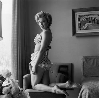 circa 1951:  Portrait of American actor Marilyn Monroe (1926 - 1962) kneeling in a chair in a two-piece polka dot bathing suit.  (Photo by Hulton Archive/Getty Images)