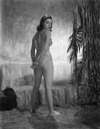circa 1955:  British actress Joan Collins poses in a checked bikini on a 'desert island' set.  (Photo by Hulton Archive/Getty Images)