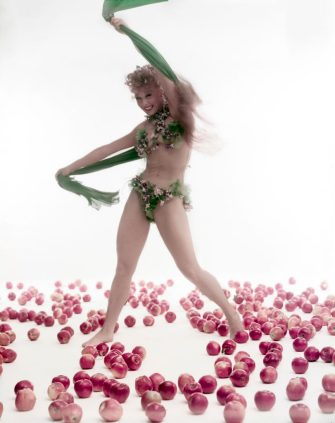 NEW YORK CITY, NEW YORK - 1953 : Dancer and choreographer Gwen Verdon is dancing wearing green bikini holding a green scarf  on a floor covered with red apples. (Photo by Tony Vaccaro/Getty Images)
