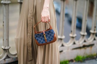 PARIS, FRANCE - JANUARY 31: Fashion blogger Xiayan wears a beige pleated long skirt from Copenhagen Muse, a blue and brown monogram printed Gucci bag made of denim and leather, on January 31, 2021 in Paris, France. (Photo by Edward Berthelot/Getty Images)