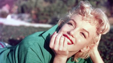 PALM SPRINGS, CA - 1954: Actress Marilyn Monroe poses for a portrait laying on the grass in 1954 in Palm Springs, California. (Photo by Baron/Hulton Archive/Getty Images)