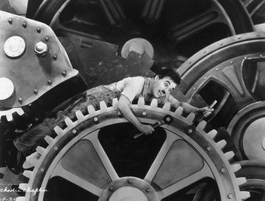 1936:  British actor and director Charles Chaplin (1889 - 1977), wearing overalls and holding a wrench, sits on an enormous set of gears in a still from Chaplin's film, 'Modern Times'.  (Photo by Hulton Archive/Getty Images)