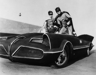 Adam West and Burt Ward as Batman and Robin atop the Batmobile, in the famously campy TV series Batman, early in the show's run in 1966.