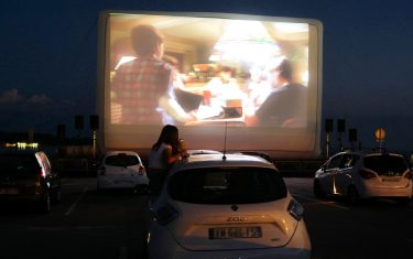 """Spectators in their vehicle attend a drive-in movie screening of """"ET"""" by US director Steven Spielberg, in the French riviera city of Cannes, southern France, on May 20, 2020, as part of """"Cannes Cine-Drive"""" while the cinemas in France are still closed due to the measures taken to curb the spread of the COVID-19 pandemic, caused by the novel coronavirus. (Photo by VALERY HACHE / AFP) (Photo by VALERY HACHE/AFP via Getty Images)"""