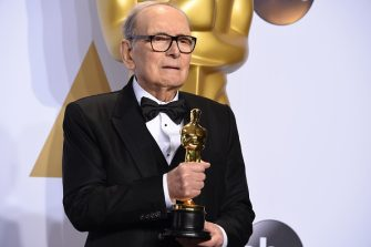 "Composer Ennio Morricone poses with the Oscar for Best Original Score, ""The Hateful Eight,"" in the press room during the 88th Oscars in Hollywood on February 28, 2016.     / AFP / Robyn BECK        (Photo credit should read ROBYN BECK/AFP via Getty Images)"