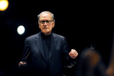 "RIMINI, ITALY - AUGUST 25:  Italian composer Ennio Morricone conducts the choir and orchestra in concert ""la Bellezza ci salvera""  on August 25, 2012 in Rimini, Italy.  (Photo by Roberto Serra - Iguana Press/Getty Images)"