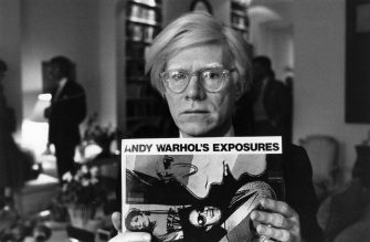 Andy Warhol (1926 - 1987), American pop artist and filmmaker, holding an example of one of his posters.  Original Publication: People Disc - HM0195   (Photo by John Minihan/Getty Images)