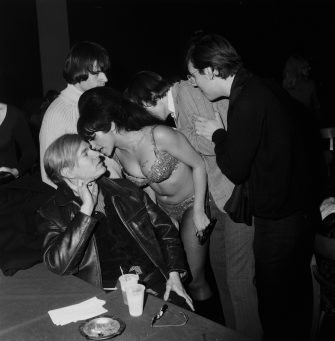 4th December 1966:  A female go-go dancer whispers into the ear of American Pop Artist Andy Warhol (1928 - 1987) during a Velvet Underground and Nico performance in a 'Freakout' party at the Action House disco, Island Park, Long Island, New York. They are surrounded by three men.  (Photo by Tim Boxer/Hulton Archive/Getty Images)