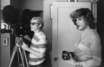 1967:  American pop artist Andy Warhol (1928 - 1987) stands behind a movie camera next to actor Mario Montez, dressed as a woman, on the set of his film, 'Chelsea Girls,' New York City.  (Photo by Santi Visalli Inc./Getty Images)