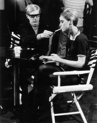 circa 1965:  American Pop artist Andy Warhol (1928 - 1987) sits next to actor Edie Sedgwick (1943 - 1971) and lights her cigarette, on the set of one of his films.  (Photo by Walter Daran/Hulton Archive/Getty Images)