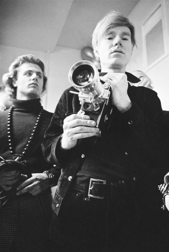 circa 1966:  American pop artist Andy Warhol (right) holds a camera fitted with a zoom lens while standing with photographer, poet, and archivist Gerard Malanga at club Paraphernalia, New York City.  (Photo by Jack Robinson/Hulton Archive/Getty Images)
