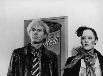 16th February 1971:  American Pop artist Andy Warhol stands next to actress Jane Forth, star of his new film 'Trash,' in front of his famous Campbell's Soup painting, in London.  (Photo by Express/Express/Getty Images)
