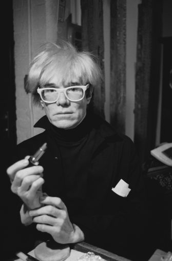 American pop artist Andy Warhol (1928 - 1987) holding a lipstick, circa 1985. (Photo by Jill Kennington/Hulton Archive/Getty Images)