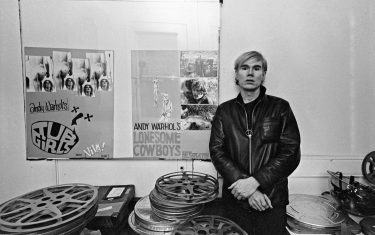 Andy Warhol at the Factory with posters for Tub Girls (1967) and Lonesome Cowboys (1968). (Photo by Jack Mitchell/Getty Images)