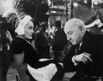 Film actress Gloria Swanson (1897-1983) and film director Cecil B DeMille (1881-1959) sitting together on the set of 'Sunset Boulevard,' a biting satire on Hollywood stardom in which DeMille plays himself, 1949.  (Photo by Hulton Archive/Getty Images)