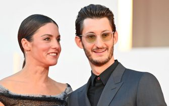 """French actor Pierre Niney and his partner Australian actress Natasha Andrews arrive for the screening of the film """"Amants"""" (Lovers) presented in competition on the second day of the 77th Venice Film Festival, on September 3, 2020 at Venice Lido, during the COVID-19 infection, caused by the novel coronavirus. (Photo by Alberto PIZZOLI / AFP) (Photo by ALBERTO PIZZOLI/AFP via Getty Images)"""