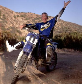 """372259 02: ***EXCLUSIVE*** (NO TABLOIDS) Austrailian-born actor George Lazenby poses on his motorcycle November 1, 1999 in Valyermo, Ca. Thirty years after his rocky one-time outing as James Bond in 1969's """"On Her Majesty's Secret Service,"""" Lazenby's life may be more tranquil now but it is still dynamic. When he's not golfing or tinkering with his tractor, he roars around on his 600-acre Valyermo, Calif. property on his four-wheeler or one of his three motorcycles. (Photo by Ann Summa/Liaison)"""