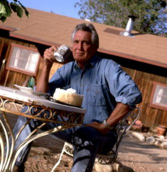 """372259 03: ***EXCLUSIVE*** (NO TABLOIDS) Austrailian-born actor George Lazenby poses at home November 1, 1999 in Valyermo, Ca. Thirty years after his rocky one-time outing as James Bond in 1969's """"On Her Majesty's Secret Service,"""" Lazenby's life may be more tranquil now but it is still dynamic. When he's not golfing or tinkering with his tractor, he roars around on his 600-acre Valyermo, Calif. property on his four-wheeler or one of his three motorcycles. (Photo by Ann Summa/Liaison)"""